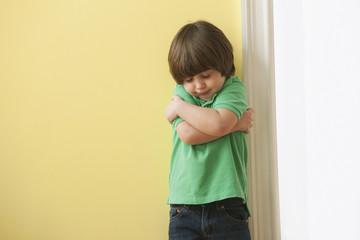 Sad Caucasian boy hugging himself