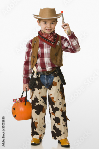 Caucasian boy in cowboy costume carrying jack o'lantern