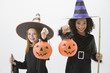 Girls in witch costumes holding jack o'lantern