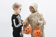 Boys in skeleton and mummy costumes trading Halloween candy