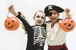 Boys in skeleton and pirate costumes holding jack o'lantern