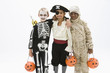 """Boys in skeleton, pirate and mummy costumes holding jack o'lantern"""