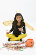 Asian girl in bee costume eating Halloween candy