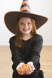Caucasian girl in witch costume holding Halloween candy