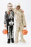 Boys in skeleton and mummy costumes holding jack o'lantern