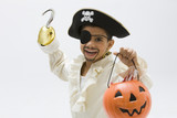 Hispanic boy in pirate costume holding jack o'lantern