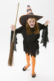 Caucasian girl in witch costume holding broom