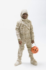 Black boy in mummy costume holding jack o'lantern