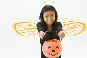 Asian girl in bee costume holding jack o'lantern