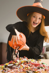 Caucasian girl in witch costume dumping out Halloween candy