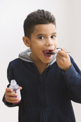 Hispanic boy taking cough medicine