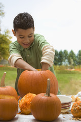Hispanic boy carving Halloween pumpkin