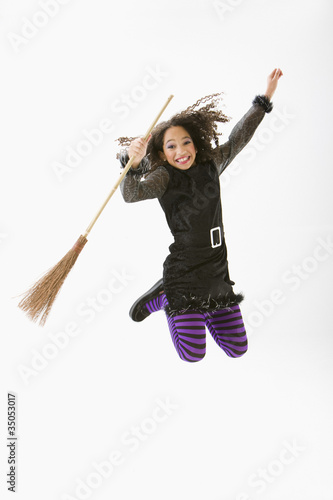 Mixed race girl in Halloween costume jumping and cheering