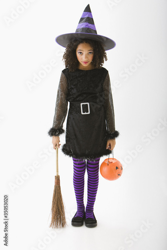 Mixed race girl in Halloween costume holding broom and jack o'lantern