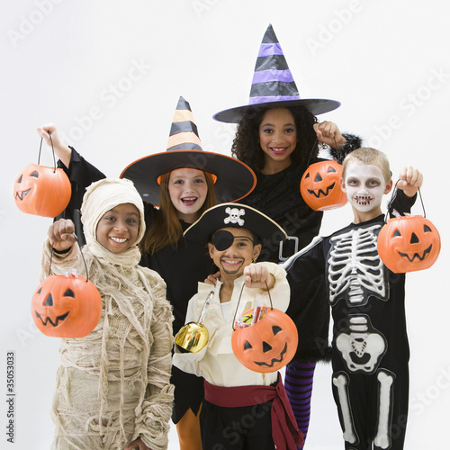 Children in Halloween costumes holding jack o'lanterns