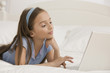 Hispanic girl using laptop on bed