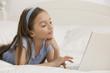 Hispanic girl using laptop on bed