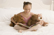 Hispanic girl in ballet tutu reading book on bed
