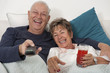 Senior Hispanic couple laying in bed watching television