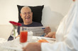 Senior Hispanic woman bringing husband breakfast in bed