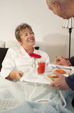 Senior Hispanic man bringing wife breakfast in bed