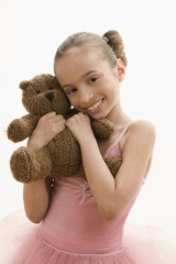 Hispanic girl in ballet tutu hugging teddy bear