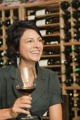 Hispanic woman drinking red wine