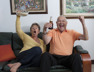 Senior Hispanic couple watching television and cheering