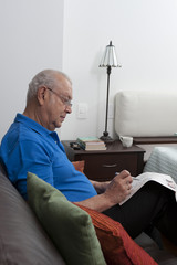 Senior Hispanic man sitting on sofa looking at newspaper