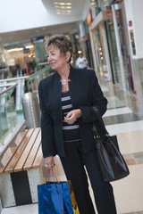 Senior Hispanic woman walking in mall with shopping bags