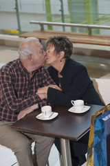 Senior Hispanic couple kissing in cafe