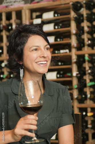 Hispanic woman drinking red wine