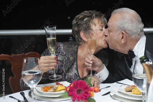 Kissing Hispanic couple toasting with Champagne in restaurant