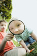 Caucasian brothers looking through magnifying glass