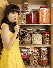 Mixed race woman taking lollipop from cupboard