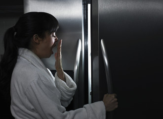Sleepy mixed race woman looking in refrigerator at night