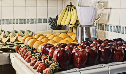 Fruits and blender in kitchen counter