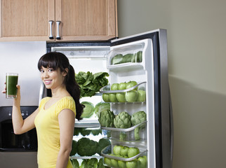 Mixed race woman drinking healthy drink near refrigerator