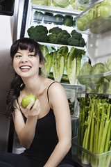 Mixed race woman with apple near green vegetables in refrigerator