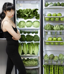 Unhappy mixed race woman looking at green vegetables in refrigerator