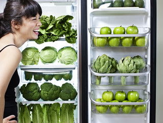Mixed race woman looking at green vegetables in refrigerator