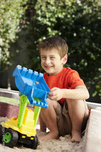Caucasian boy playing in sandbox