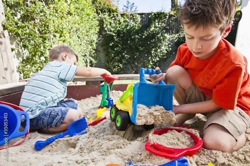 Caucasian brothers playing in sandbox