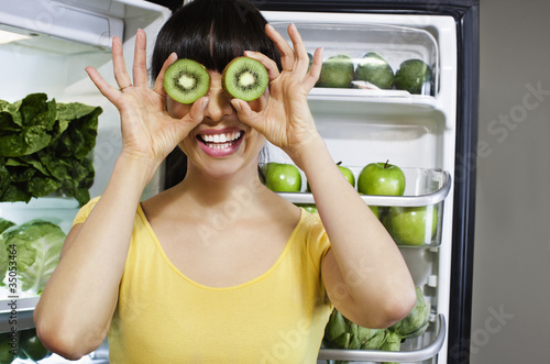 Mixed race woman covering eyes with kiwi slices near refrigerator