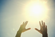 Mixed race woman's hands reaching toward sun