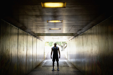Mixed race man standing in tunnel