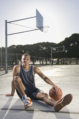 Mixed race man sitting with basketball