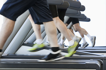 People running on treadmills in health club