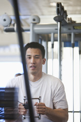 Chinese man lifting weights in health club