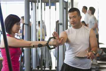 Woman working with personal trainer in health club
